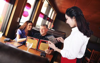 Happy mature waiter taking order from couple at restaurant
